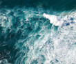 Turquoise seawater with foamy waves, picture from above, abstract ocean background and texture