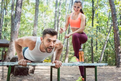 Sportowy człowiek robi push-up w odkrytym siłowni, jego dziewczyna go obserwuje