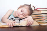 A little girl in glasses fell asleep behind textbooks - 201175346