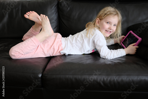 blondes mädchen mit tablet auf dem leder sofa