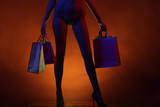 Erotic shopping. Sex shop, goods for adults. Unrecognizable woman in pantyhose without underwear with shopping bags. Young girl spends money. Shopping for women. Model in heels buys lingerie