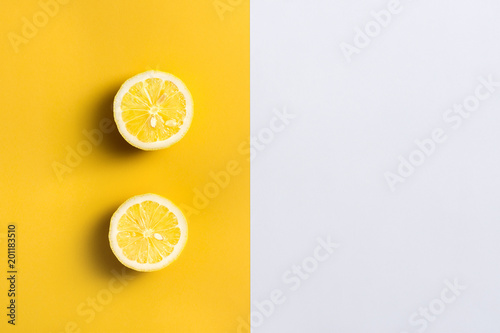 Foto Murales Lemon halves on split color, yellow and white background with copy space for text.