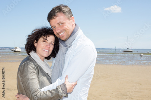 A picture of a middle aged couple walking along the beach in love outdoors
