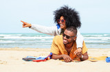 Young afro american couple  pointing finger relaxing on beach - Cheerful african friends having fun at day on blue ocean background - Concept of lovers happy moments on summer holiday - 201195992