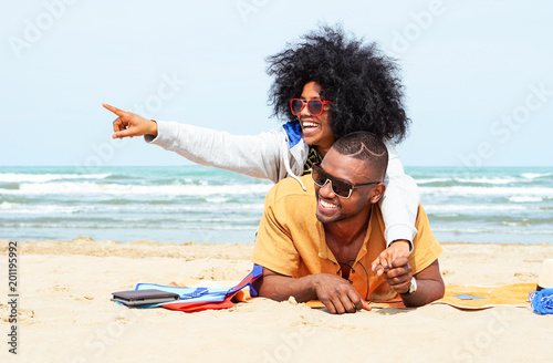 young afro american couple pointing finger relaxing on beach