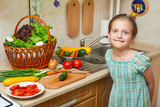 Child girl cooking in home kitchen. Basket of vegetables and fresh fruits in kitchen interior. Healthy food concept