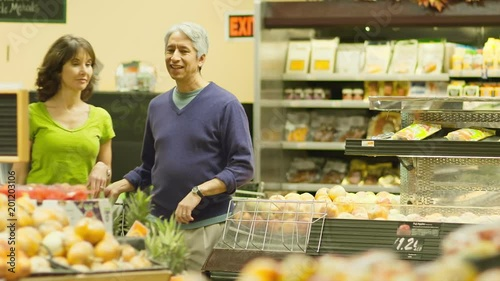 An older couple walk through a produce section and check out the food together