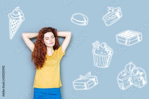 Ulubione słodycze. Spokojna marzycielska kobieta zamyka oczy i myśli o pysznych słodyczach będąc na diecie