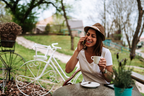 Smiling woman in cafe talking on phone and drinking coffee. - 201207737