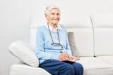 Glückliche alte Frau sitzt auf dem Sofa - 201208340