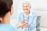 Pflegehilfe gibt Seniorin ein Glas Wasser