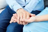 Altenpfleger hält tröstend Hand einer alten Frau - 201208381