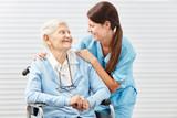 Krankenschwester mit einer alten Frau im Rollstuhl