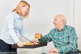 Junge Frau serviert Senior das Frühstück