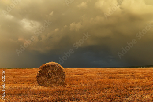 The harvested field, a round stack of straw and a stormy sky. The expanse of fields.
