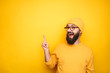 Excited hipster pointing up on yellow