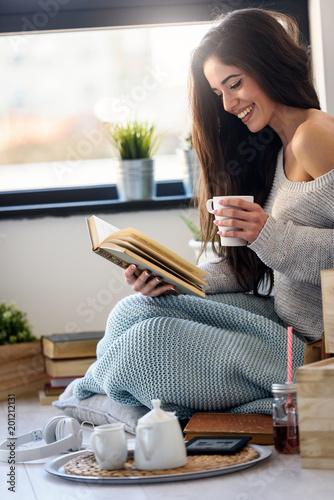 Piękna młoda kobieta czyta książkę, cieszy się okno w nowożytnym mieszkaniu.