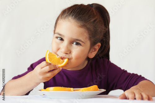 Foto Murales little cute child girl dressed in a purple blouse holding an orange and eating off a piece of orange
