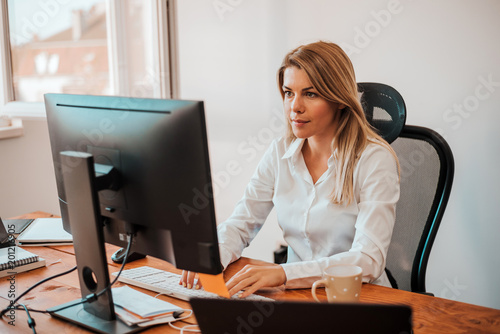 Blonde business woman working on a computer.