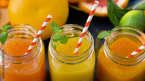 healthy eating, drinks, diet and detox concept - close up of fresh fruit or vegetable juices in mason jar glasses with straws on kitchen table