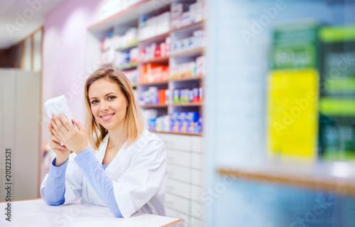 Plexiglas Apotheek Portrait of a young friendly female pharmacist.