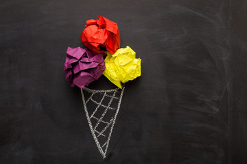 Drawn ice-cream cone and crumpled paper balls on black background