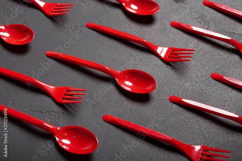 Top view on plastic forks and spoons on black background