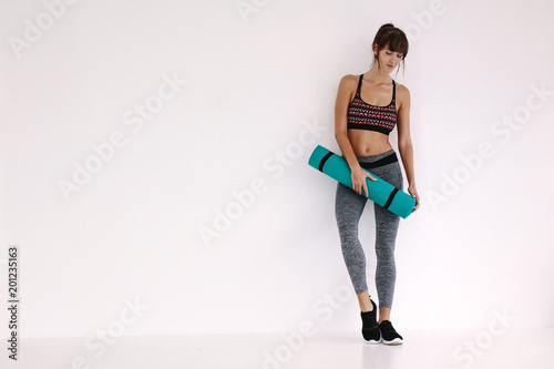 Woman standing with yoga mat in studio