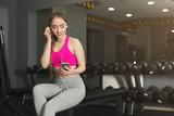 Fitness girl in headphones choose music on phone - 201239976