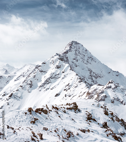 The top of the mountain against the cloudy sky. Alpine landscape and snow-capped peaks - 201241536