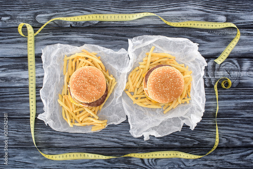 Sticker top view of two hamburgers with french fries and measuring tape on wooden table
