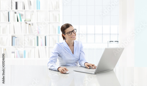 Business smiling woman or a clerk working at her office desk with computer, she is wearing eyeglasses