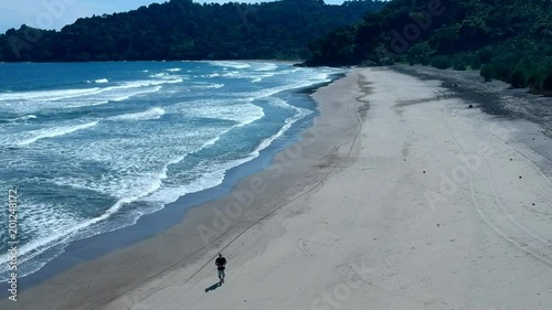 Aerial view of man walking along the beach in Indonesia at the Indian ocean