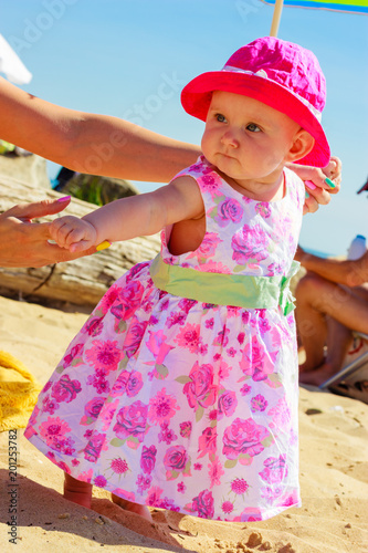 Child holding adult hands on beach