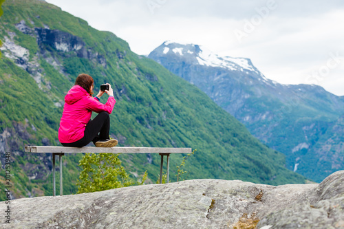 Foto Murales Tourist with camera looking at scenic view in mountains Norway