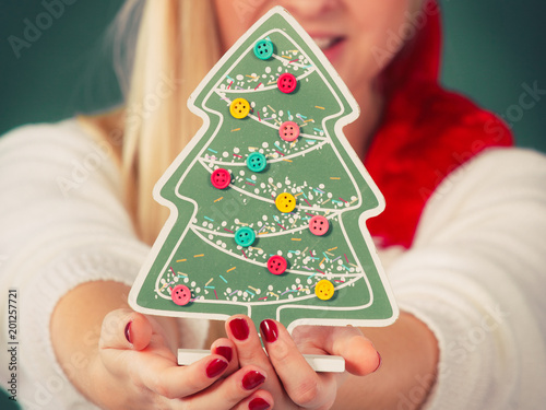 Woman holding decorative christmas tree