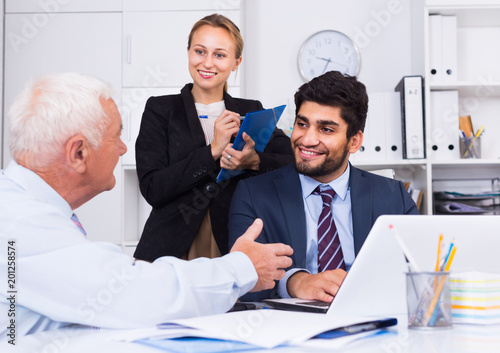 Mature male is talking to colleague