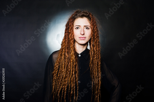 Foto Murales Studio shoot of girl in black with dreads at black background.
