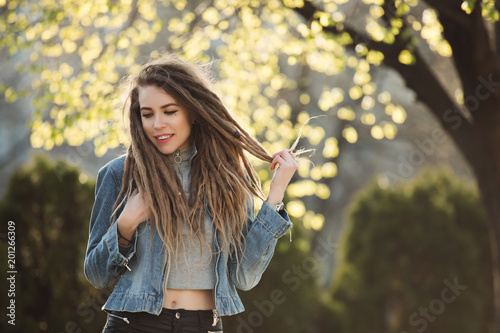 Smiling portrait of fashionable woman with dreadlocks at springtime