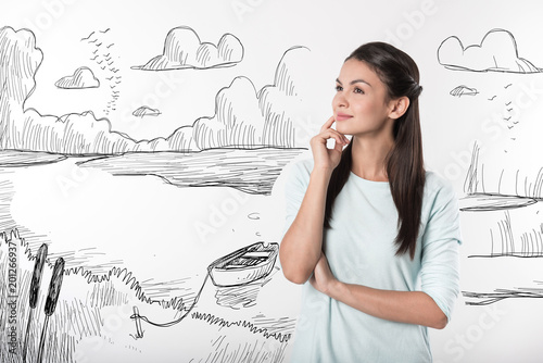 Peaceful nature. Beautiful young student smiling and thoughtfully touching her face while admiring the beauty of nature