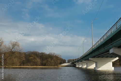 Wall mural Long concrete bridge over broad river, blue sky for background