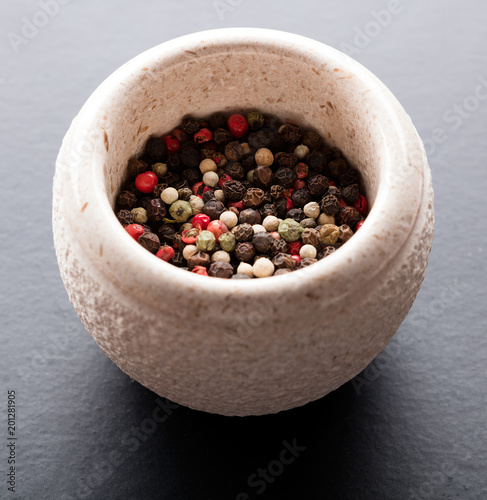peppercorns in stone bowl on gray slate background - 201281905