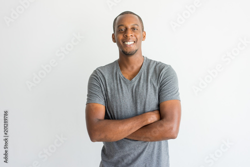 Foto Murales Happy excited young African man crossing arms on chest and looking at camera. Optimistic confident handsome guy in t-shirt smiling. Joy concept