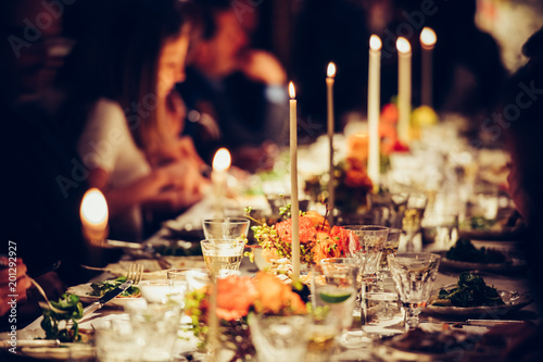 People enjoy a family dinner with candles. Big table served with food and beverages. - 201292927