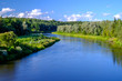 Bank of Gauja River in Latvia with blue sky and white clouds reflecting in water