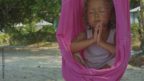 Obraz na płótnie Little cute child girl doing yoga exersice with hammock on the beach.