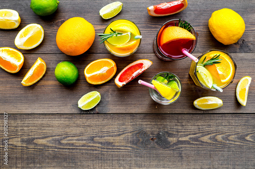 Tropical fruit cocktail with alcohol. Glass with beverage near oranges, grapefruit, lime and rosemary on dark wooden background top view space for text