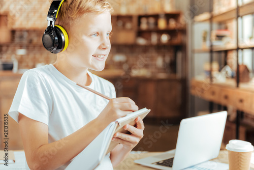 Sudden inspiration. Joyful happy positive boy wearing headphones and taking notes while listening to music