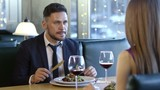 PAN of bearded man in suit and his unrecognizable girlfriend chatting and drinking wine on dinner date in restaurant - 201318342