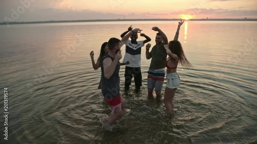 Medium shot of happy young people dancing in lake on summer evening